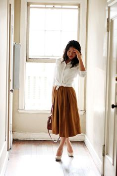A crisp white button-up looks very classy and feminine with a colorful midi skirt.  Tie it in front like so, or try tucking it in and cinching at your natural waist with a chunky belt.   Re-create this look at http://picvpic.com!
