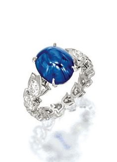 SAPPHIRE AND DIAMOND RING, CARTIER    Centring on a sugar loaf cabochon sapphire weighing 7.63 carats, to a stylised shank bezel-set with brilliant-cut diamonds together weighing approximately 1.90 carats, mounted in platinum, signed and numbered 69341A.