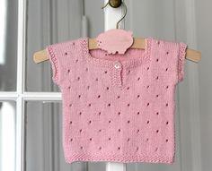 """En lille kortærmet T-shirt eller vest er suveræn som det lille """"ekstra"""" lag, når baby skal holdes varm på den lækre måde. Den lyserøde i hulstrik er strikket i bomuld/akryl og den gråmelerede i strukturmønster er i baby merinould – begge dele ultra bløde. Strikkeopskrift får du i 3 størrelser. Materialer til den grå model i blød uld kan købes…"""