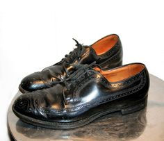 These are classic 1960s mens black leather wingtip oxfords, size 9. They are sturdy but pliable leather with perforated trim and black cloth shoe