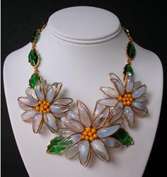 """Histoire de Verre Marquerite Daisy Necklace features three poured glass daisy blossoms of translucent poured glass and yellow glass stamens. Necklace is completed by emerald green glass leaves in a goldtone frame. Necklace is 16 """". Price $1250 / www.valerieg.com"""
