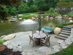 Landscaped pond with pond to pond waterfall/boulders & large bluestone quarry slab stone patio