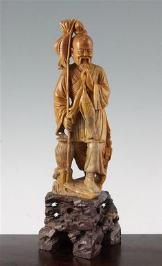 A Chinese soapstone figure of a fisherman, early 20th century, the standing figure of the fisherman holding a fish in an ochre coloured stone, on a dark brown soapstone rockwork base, 36cm.