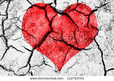 natural red heart shape in cracked dry soil - stock photo