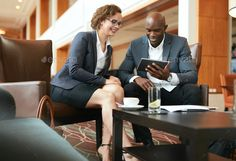 Business people discussing project on digital tablet by jacoblund. Two business people sitting at coffee shop discussing project on digital tablet. Young businesswoman and businessman ...