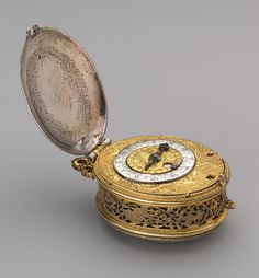 Clock watch with calendar, ca. 1600-1610  Movement probably by Nicolas Forfaict the Elder (French, recorded 1573–1619)  Case: silver and gilded brass; Dial: gilded brass and silver, with a steel hand; Movement: gilded brass and steel, partly blued