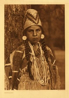 "Umatilla Maid (1905) by Edward S. Curtis - ""Two distinct cultural areas are represented in the costume of this damsel. The familiar beadworked, deerskin dress is an acquisition from the plains culture, while the basketry hat and the shell-bead necklace hail from the pacific slope. Note the skin of the deer's tail fastened in front at the collar, as an aid in removing the garment."""