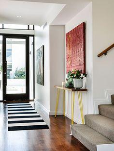 entrada con una consola vintage de una casa relajada y luminosa
