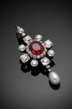 A fine Victorian red spinel, diamond and pearl pendant/brooch. Set with an oval-cut red spinel to the centre, surrounded by circular-cut diamonds forming an oval cluster within a frame of four square and four circular-cut diamonds and suspending an egg-shaped pearl on pendant drop and with a diamond-set detachable top loop, mounted in silver on gold and with detachable brooch pin in fitted case by Harvey and Gore of London, spinel with estimated weight of 5.50cts.