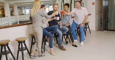 People Clinking with Cups of Coffee by Daniel_Dash Group of people in casual clothes sitting on bar stools during break and clinking with cups of coffee.