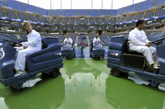 Workers dealing with the rain prior to the Men's Singles Semifinals on Day 13 of the 2012 US Open. - Getty Images