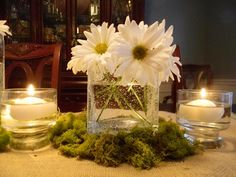 This table-length centerpiece uses daisies and reindeer moss paired with a burlap runner for a nature-inspired look. Small floating candles add a romantic element to this setting