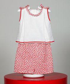 Conjunto de niña compuesto por camisa y pantalón. Camisa blanca con detalles rojos en sisa y bajo de la misma. Detalles florales en cuello y lazos de hombros. Pantalón con estampado floral. www.chatitaonline.com