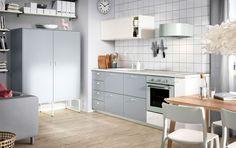 Kök med vita dörrar och grå lådor, kombinerat med gröngrå vitvaror.