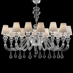 An alternative version of a very successful chandelier. Following the lines of Ran Front and Ran Side, this collection returns to the classic outline of a chandelier: a circular version, with ten, fourteen or eighteen arms and an oval version with eight, twelve or twenty arms, as well as the wall lamp with two lights.