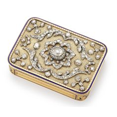 A Swiss or Austrian gold, enamel and diamond-set rectangular snuff box, circa 1830 the top set with diamond scrollwork surrounding a central rose-cut diamond of 2.48 carats, all edged in blue enamel, the sides chased with strips of ornament in blue enamel frames, with partly-enameled palmette and wreath motifs at the corners.