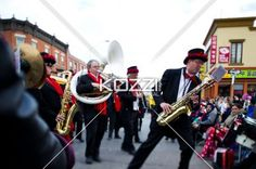 view of a marching musical band at christmas parade. - View of a marching musical band playing trumpet at Christmas parade.