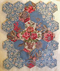 After looking at a fabulous antique hexagon quilt shown in the book The Fabric of Society by Annette Gero,she cames up with this little diamond shape with an appliqued insert of a pretty basket fabric.