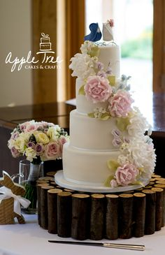 Elegant 4-tier white wedding cake, decorated with handmade sugar flowers - roses, blossoms, sweet peas, buds and foliage.
