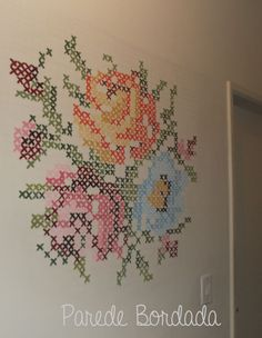 cross stitch flowers painted on a wall: