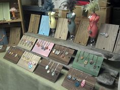 Sandra DeYoung Niese's Display. Small rectangles of paneling with hole drilled for peg (angle so pendants don't slide).