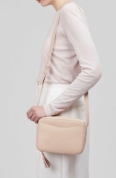 The ideal everyday bag that showcases a simple silhouette with clean, feminine lines. This compact piece was designed with a simple C-curve at the front for easy access to your phone or other items. Carefully crafted in Turkey from pebbled-leather, this piece is finished with a large tassel zip pull for an elevated accent.