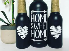 This is a set of three black spray painted alcohol bottles. The larger one is a wine bottle and the two smaller ones are beer bottles. The wine bottle is decorated with the saying home sweet home and the two beer bottles have matching white hearts. All three bottles have twine wrapped