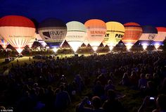 Balloons are illuminated by their burners during a dusk display at the Bristol Internation...