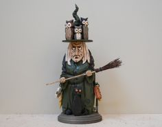 """This grumpy witch can't seem to keep the pesky owls off her hat! She stands 13"""" tall and is hand carved from 4"""" thick basswood. She has lots of ornaments hanging from her waist. ($525)"""
