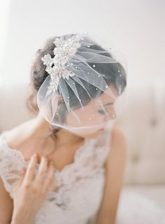 This crystal lace birdcage veil is made of a gorgeous crystal floral lace that is sewn to a handmade tulle birdcage veil, and then finished with many scattered crystals throughout. It measures approximately 11 long and it is attached to a silver plated comb. - Hand cut and sewn