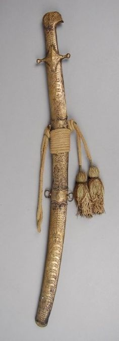 Sword and sword-sheath. Wooden sheath is encased in brass (?) with piercedwork and incised and stamped motifs. With textile tassels.