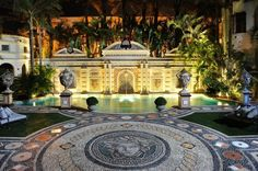 """Versace's """"Casa Casuarina"""" has ornate mosaic tile flooring, pools, decorative urns, neo-classical style, green lawns, lounge furniture, and over the top aesthetic."""
