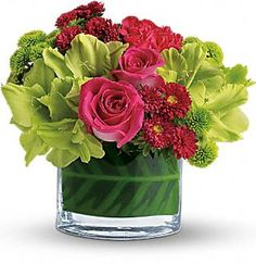 Hot pink roses and miniature carnations, bright green gladioli and button mums, and soft red matsumoto asters are delivered in an oval vase of clear glass.