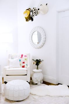 White minimalist nursery for the baby with stuffed animal wall art and white pouf