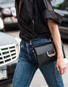 Street Style. Classic outfit to copy. Leather black handbag, black tee and blue classic denim.