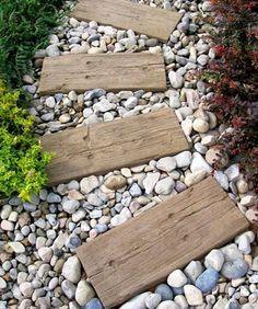 Une élégante allée de jardin fait à partir de planches de palette en bois posées sur du gravier de cailloux de divers couleurs, en accord avec les plantes autour.
