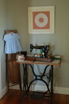 Singer 201 sewing machine on top of a treadle stand, wooden ironing board.