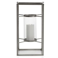 Angular, modern and crisp our exclusive Tribecca lantern is a striking way to add candle glow to a room. An open frame, cast out of a matte finished nickel plated iron, anchors a floating pedestal pillar candle holder. Distinctively suspended between its exterior frame, a tall glass hurricane surrounds the entire pedestal, protecting the flame within.  9.45 w 18.9 h  $50  Dimensions 9.45W x 18.9H