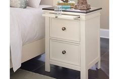 The Woodanville nightstand's stance on cottage-quaint style is a breath of fresh air. Its crisp, linear profile is beautified with picture frame drawer fronts and bronze-tone knobs. But what's really distinctive: its wood tone over antique white finish exuding richness and added dimension. The convenience of a pullout tray goes a long way.