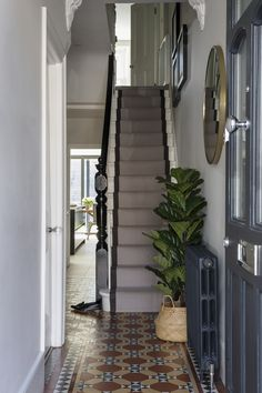 Interior Design by Imperfect Interiors at this Victorian terraced house in Balham, London. A palette of contemporary paint colours mixed with traditional period details- white walls, black column radiator, potted plant & original Victorian floor tiles make the entrance hallway feel elegant & contemporary. Photo by Chris Snook
