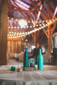 Shades of blue bottles with a burlap table runner in a lodge #wedding.