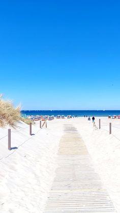 Holzweg am Strand von Warnemünde. Blauer Himmel im Sommer an der Ostsee.