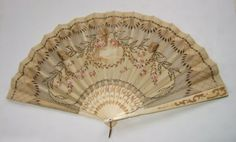 Antique Ladies Fan with Gold and Pink Details. This lovely ladies fan of silk, is heavily accented with gold thread, sequins and painting. There are also delicate pink roses with a pastoral scene at the center. Gold detailing on the fan edges and at its base. From the early 1900's.