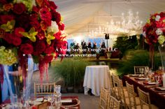Tented wedding reception with hanging chandeliers and red flowers with green accents.