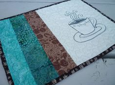 a cuppa' coffee mug rug quilted placemat with thread sketch on muslin with aqua teal and brown patchwork