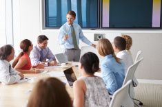 Motivational Speaker Talking To Businesspeople In Boardroom stock photo