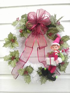 This Christmas Winter or Holiday wreath for your Front Door or Decoration features a white faux snow fringed covered Styrofoam wreath decorated with holly berries and leaves glittery with sequins. A glittery organza red ribbon falls from the top and an Elf carrying a gift sits on the side of the wreath. Based on a large styrofoam base this wreath measures grapevine base, this wreath measures 18 all around and is 5 deep. This wreath would be wonderful for your Christmas door because it can…