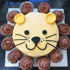For a second birthday party, a lion cake. An 8 inch sponge cake, covered in orange-tinted buttercream. Sugarpaste ears, eyes, nose, mouth and whiskers. Chocolate cupcakes around the edge for the mane.