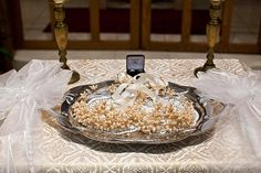 Greek Orthodox wedding crowns on tray with rings and candles
