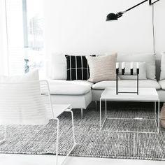 Olohuoneen pelkistetyn tyylikäs ilme ja kauniin kevytrakenteiset Hay Hee nojatuoli ja Hay tarjotinpöytä. Musta Flos valaisin seinällä tuo kivasti syvyyttä kokonaisuuteen.